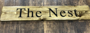 The Ness sign printed on solid wood and varnished
